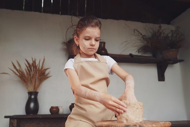 Urocza rzemieślnicza mała dziewczynka cieszy się sztuką ceramiki i procesem produkcyjnym