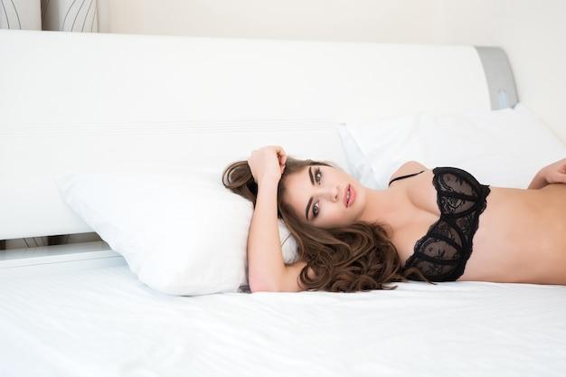 Urocza seksowna kobieta w czarnej bieliźnie leżąca na łóżku i patrząca na kamerę