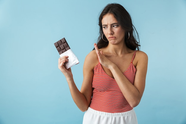 Urocza sfrustrowana dziewczyna ubrana w letnie ubrania stojąc na białym tle nad niebieskim, trzymając tabliczkę czekolady