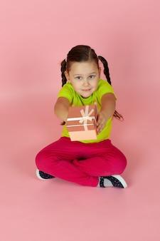 Urocza śliczna dziewczyna w jasnozielonej koszulce i czerwonych spodniach wręcza nam pudełko prezentowe
