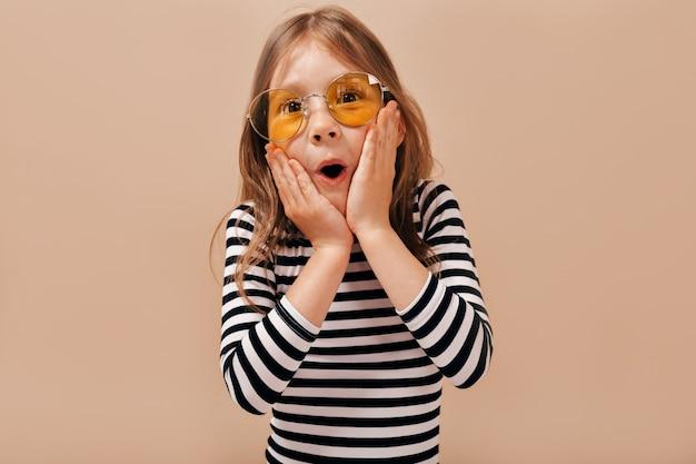 Urocza śliczna mała 6-letnia dziewczynka z jasnymi włosami w koszuli w paski pozuje z otwartymi ustami i trzyma ręce na czeku