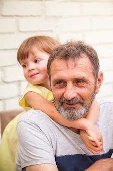 Urocza śliczna mała dziewczynka przytulająca swojego brodatego dziadka
