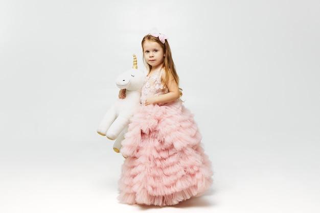Urocza śliczna mała dziewczynka ubrana jak księżniczka w różowej spódnicy, pozowanie na białym tle i trzymając pod pachą pluszową zabawkę jednorożca