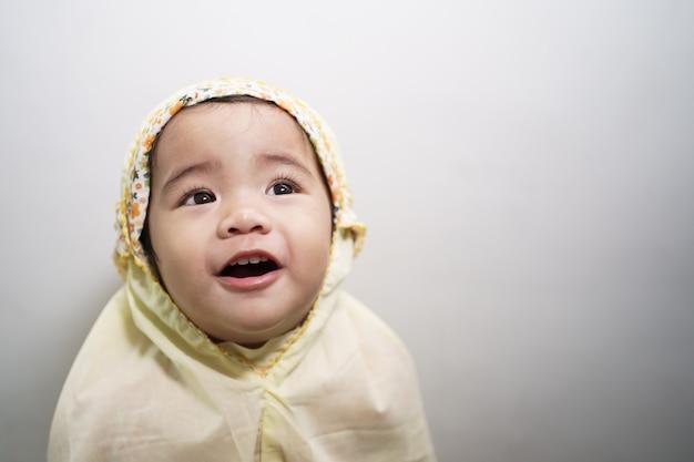 Urocza śliczna mała dziewczynka ubrana w muzułmański szalik hidżabu uśmiecha się