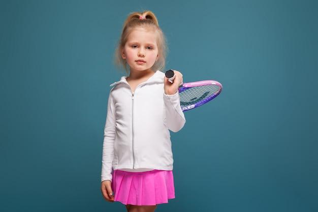 Urocza śliczna mała dziewczynka w białej koszula, białej kurtce i menchii spódnicie z tenisowym kantem