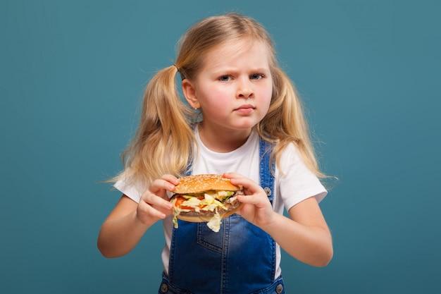 Urocza śliczna mała dziewczynka w białej koszula i cajgowym kombinezonie z hamburgerem
