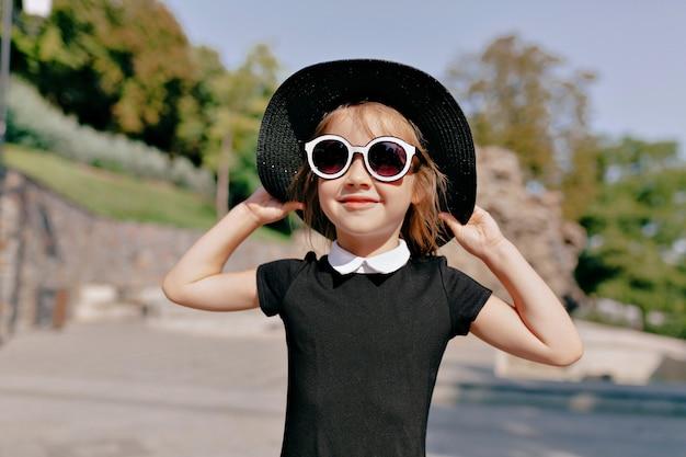 Urocza śliczna mała dziewczynka w kapeluszu i okularach przeciwsłonecznych spaceru w parku w słoneczny, ciepły dzień