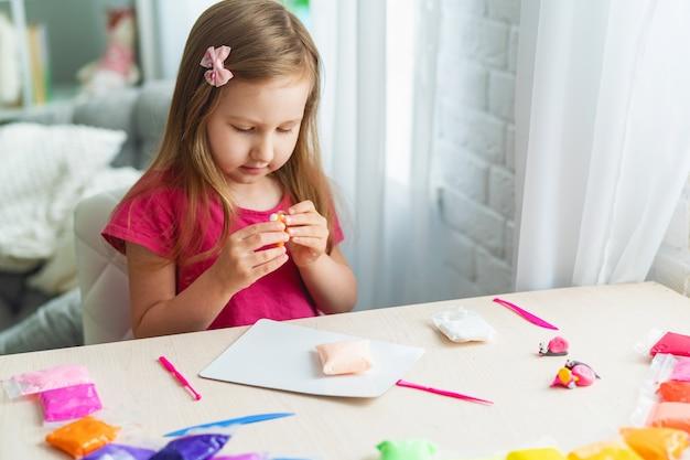 Urocza śliczna mała dziewczynka z miękką kolorową glinką
