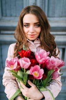 Urocza śliczna niesamowita brunetki dziewczyna stoi przed starymi błękitnymi drzwiami z bukietem świeżych tulipanów. dzień kobiet. 8 marca. piękna nastolatka z dużą ilością kwiatów jako prezent od chłopaka.