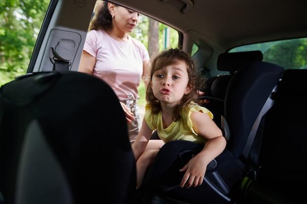 Urocza smutna dziewczynka w foteliku samochodowym. matka zapinająca córkę pasem bezpieczeństwa dla bezpiecznego poruszania się dzieci w samochodzie