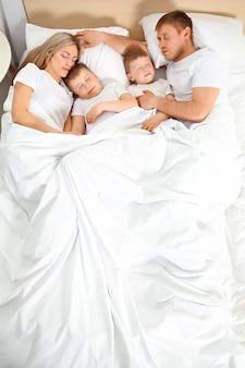 Urocza śpiąca rodzina w łóżku