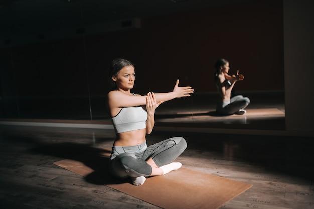 Urocza sportowa brunetka siedzi na macie ze skrzyżowanymi nogami i wyciągając rękę.