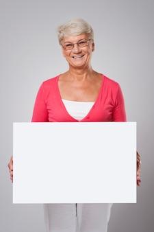 Urocza starsza kobieta obejmująca tablicą