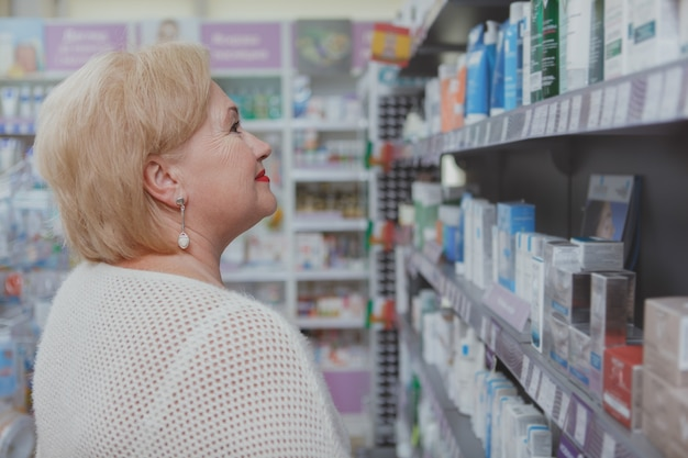 Urocza starsza kobieta robi zakupy w aptece