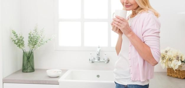 Urocza starsza kobieta słuzyć kawę w domu