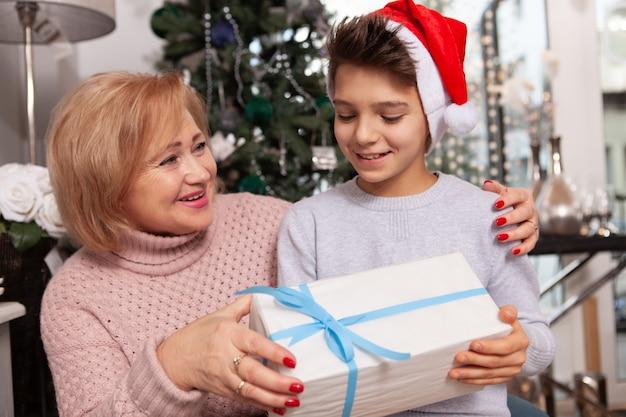 Urocza starsza kobieta świętuje boże narodzenia z jej wnukiem