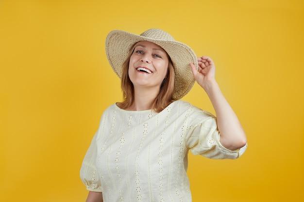 Urocza starsza kobieta w słomkowym kapeluszu uśmiecha się patrząc w kamerę na jasnym tle żółtym pojęcie letniej sprzedaży, wakacji, podróży.