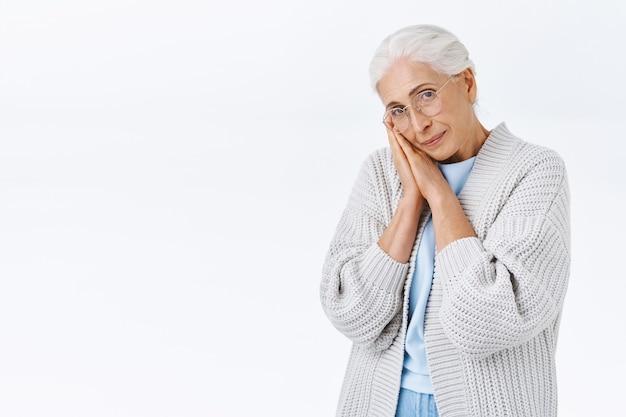 Urocza starsza pani z siwymi uczesanymi włosami, w okularach pochylona twarz na dłoniach i wpatrująca się w kamerę smutna lub samotna, sfrustrowana starzeniem się i zmarszczkami, przywołuje wspomnienia młodości, biała ściana