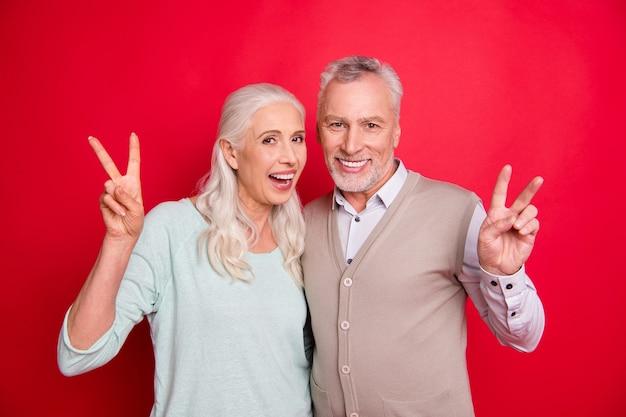 Urocza starsza para pozuje na czerwonej ścianie