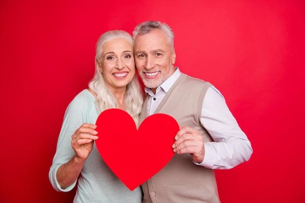 Urocza starsza para pozuje razem przy czerwonej ścianie