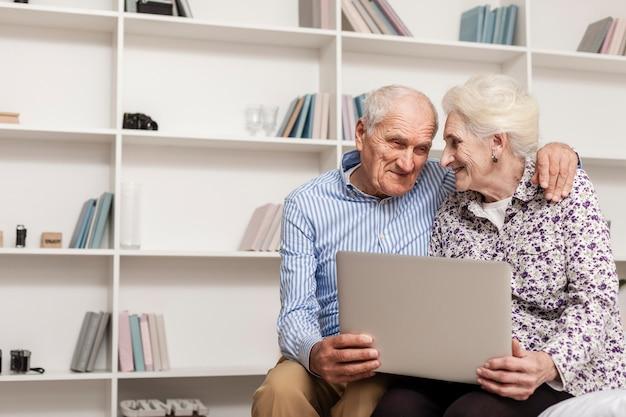 Urocza starsza para trzyma laptop