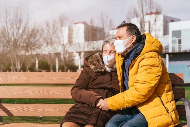 Urocza starsza para w maskach medycznych relaksująca się na ławce w parku