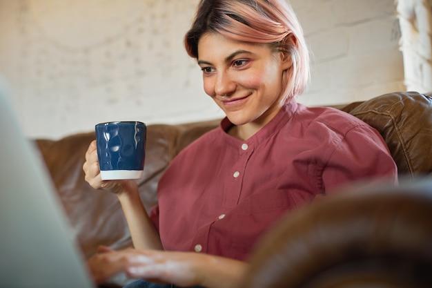 Urocza studencka dziewczyna w dobrym nastroju, relaks w domu i picie kawy