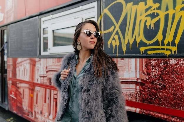 Urocza stylowa dama z długimi falującymi włosami w futrze pozująca podczas plenerowej sesji zdjęciowej.