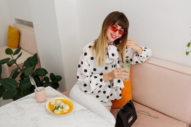 Urocza stylowa kobieta cieszy się śniadanie w kawiarni