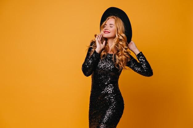Urocza stylowa kobieta pozuje w kapeluszu. pełen wdzięku blondynka długowłosy dziewczyna stojąc na żółtej ścianie.