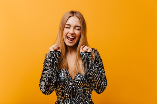 Urocza stylowa kobieta wyrażająca szczęście i uśmiechnięta. pozytywna piękna kobieta w błyszczącej kurtce stojącej na pomarańczowo