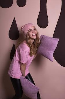 Urocza szczęśliwa blond modelka bawiąca się poduszkami na różowym tle studia