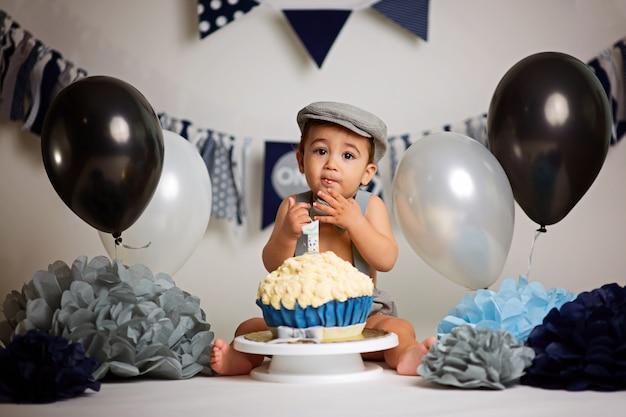 Urocza szczęśliwa chłopiec z tortem z okazji urodzin