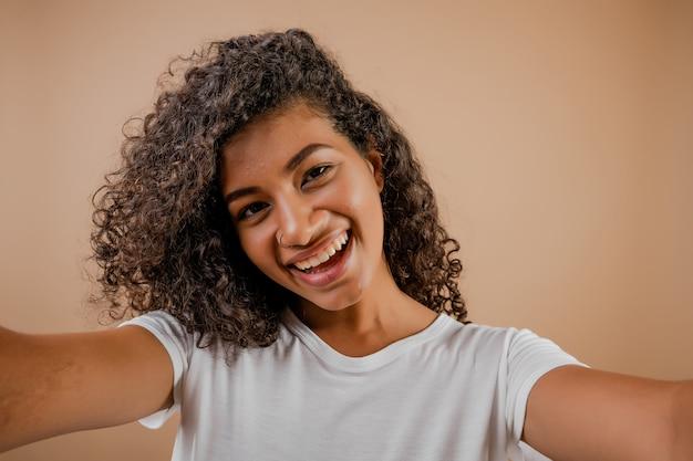 Urocza szczęśliwa czarna młoda kobieta robi selfie odizolowywającemu nad brązem