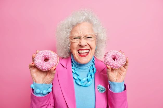 Urocza szczęśliwa dojrzała kobieta uśmiecha się szeroko, pokazuje białe idealne zęby, trzyma dwa glazurowane pączki ubrane w modne świąteczne ciuchy z biżuterią