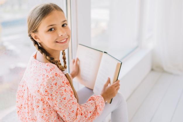 Urocza szczęśliwa dziewczyna pozuje z książką
