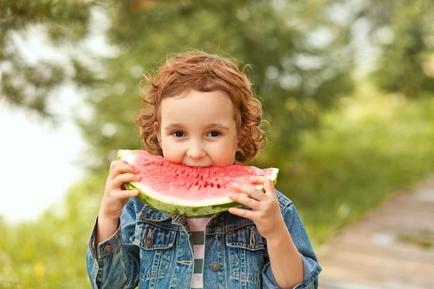 Urocza szczęśliwa dziewczyna zjada kawałek dojrzałego arbuza na zewnątrz.