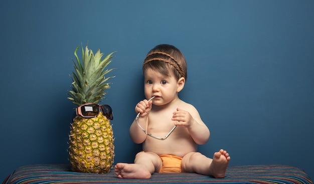 Urocza szczęśliwa dziewczynka siedzi bawiąc się ananasem na niebieskim tle