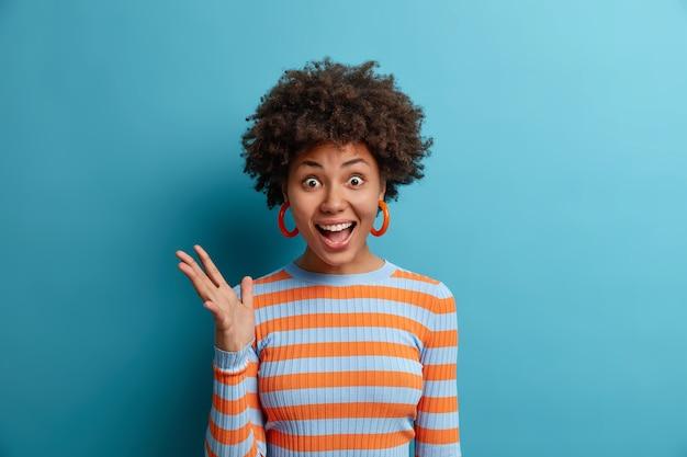 Urocza szczęśliwa, kręcona kobieta wygląda na pełną niedowierzania, podnosi rękę i woła z radością, dostaje doskonałą wiadomość lub przyjemny prezent ubrany niedbale na niebieskiej ścianie. pozytywna reakcja ludzka, emocje