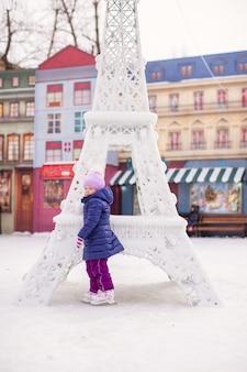 Urocza szczęśliwa mała dziewczynka cieszy się jeździć na łyżwach przy lodowiskiem