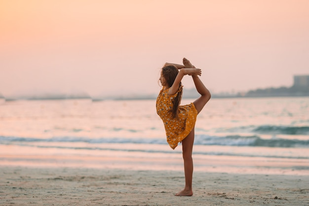 Urocza szczęśliwa mała dziewczynka na białej plaży o zachodzie słońca.