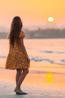 Urocza szczęśliwa mała dziewczynka na białej plaży o zachodzie słońca