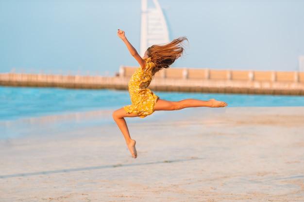 Urocza szczęśliwa mała dziewczynka na biel plaży przy zmierzchem.