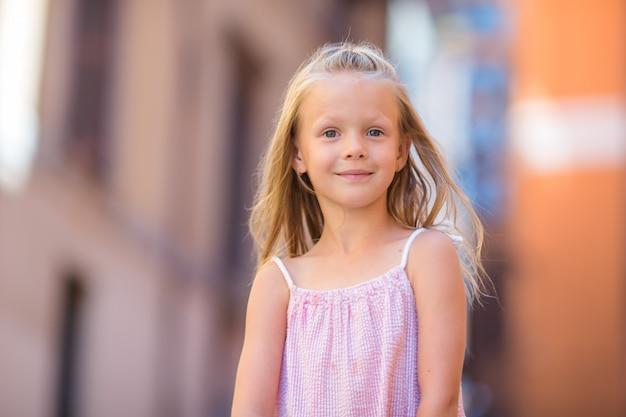 Urocza szczęśliwa mała dziewczynka outdoors w włoskim mieście. portret caucasian dzieciak cieszy się wakacje w rzym