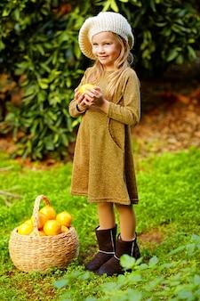 Urocza szczęśliwa mała dziewczynka z koszem pełnym dojrzałej smakowitej mandarynki i apelsinov. kolekcja cytrusów.