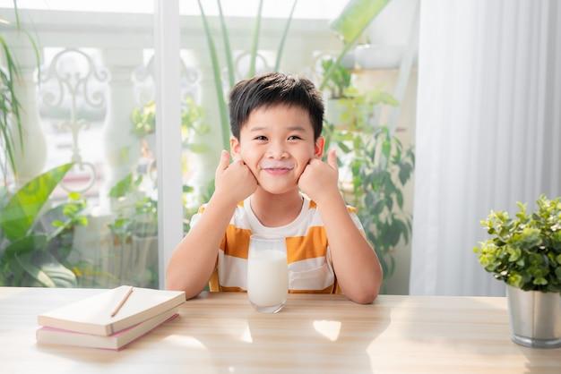 Urocza szczęśliwa młoda azjatycka chłopiec ma śniadanie i pije mleko w domu rano; patrząc w kamerę
