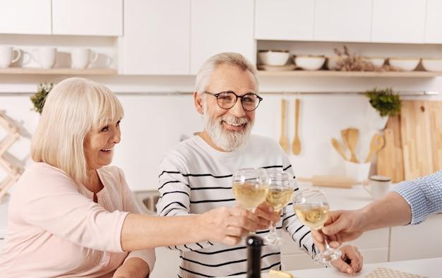 Urocza szczęśliwa para na emeryturze, która je obiad i świętuje z rodziną, podnosząc kieliszki pełne szampana