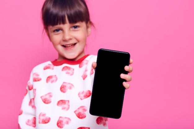 Urocza szczęśliwa uśmiechnięta dziewczynka ubrana w sweter w stylu casual i pokazująca pusty ekran telefonu komórkowego w dłoni, pozowanie na białym tle nad różową ścianą.