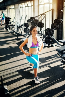 Urocza szczupła dziewczyna robi stepowanie na siłowni mając ręcznik na szyi.