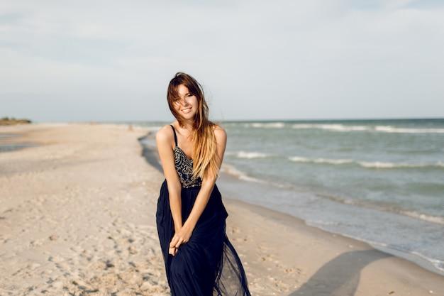 Urocza szczupła kobieta w niebieskiej eleganckiej sukience pozowanie na słonecznej plaży, w pobliżu oceanu. wietrzne włosy. idealny, szczery uśmiech.